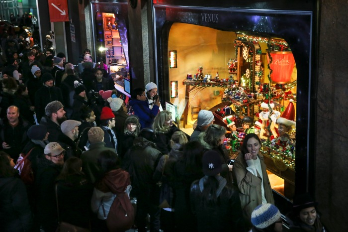 crowd of shoppers outside a store with a holiday display in the window