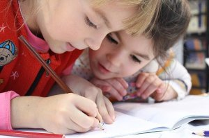 Photo of two children working on schoolwork
