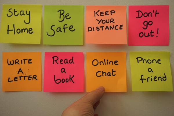 multicolored post-its on a wall with phrases 'stay home,' 'be safe,' 'keep your distance,' and other self-care advice
