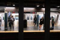 Photo of people waiting on a subway platform in New York City
